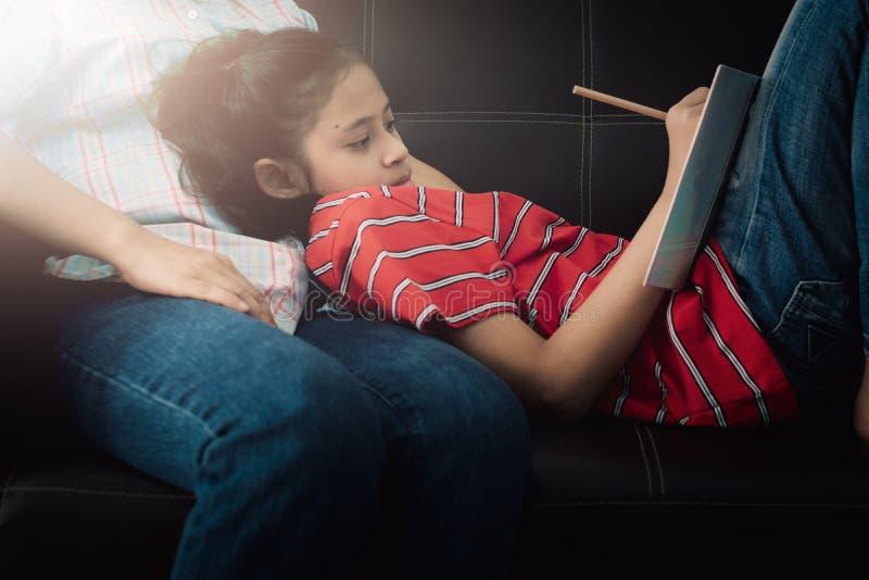 Dochter die op haar moeder bepalen en thuiswerk doen thuis onder het warme licht stock afbeeldingen