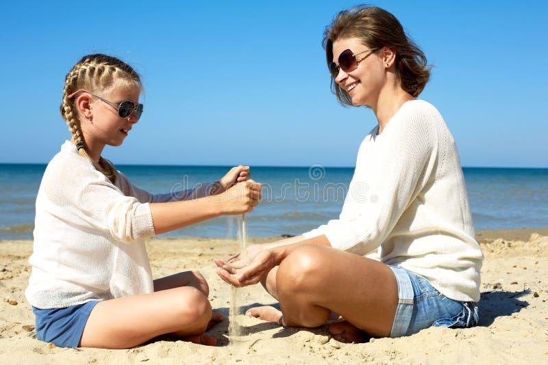 Dochter en haar mamma die met zand op het strand spelen royalty-vrije stock afbeelding