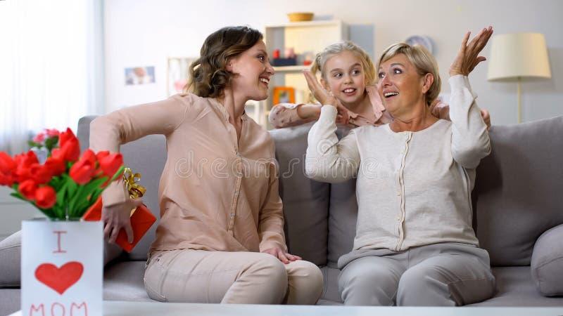 Dochter en kleindochter die verraste oma met verjaardag, liefde gelukwensen royalty-vrije stock afbeeldingen