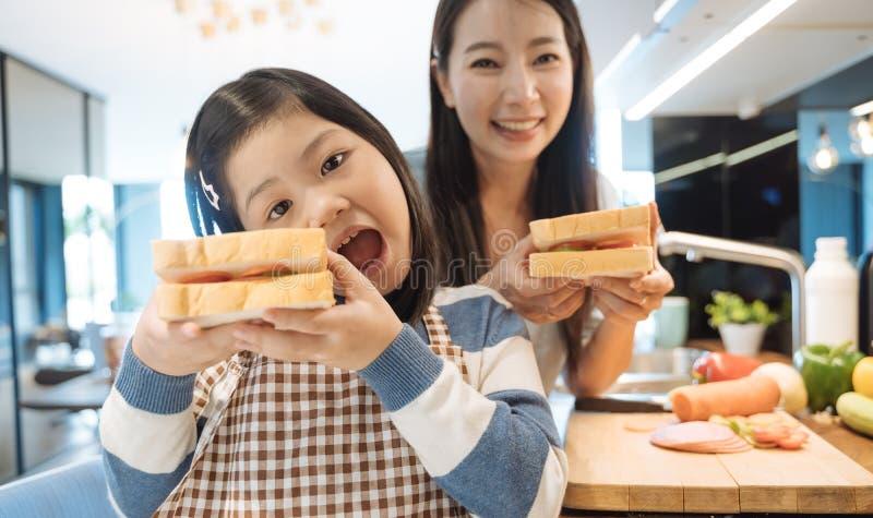Dochter en moeder die de sandwich en de salade voor ontbijt in keuken voorbereiden stock afbeelding