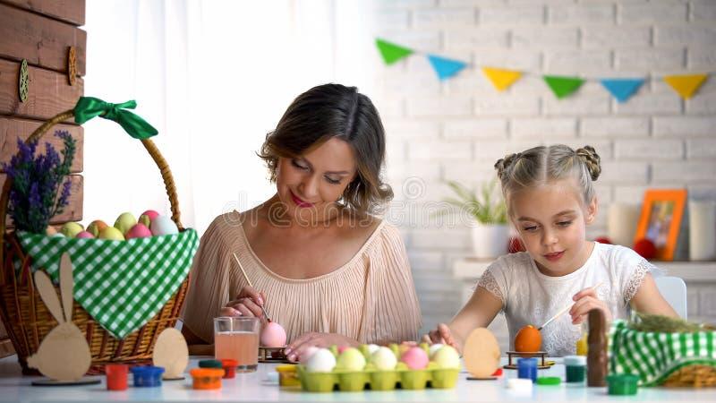 Dochter en moeder die paaseieren met kleurrijke kleurstof schilderen die voor fest voorbereidingen treffen stock foto's