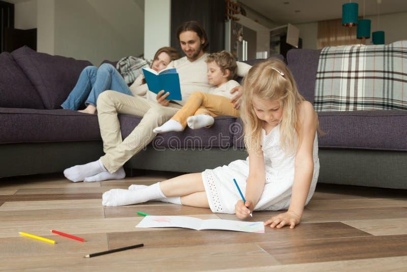 Dochter het spelen op vloer terwijl ouders en zoons de lezing boekt royalty-vrije stock foto's