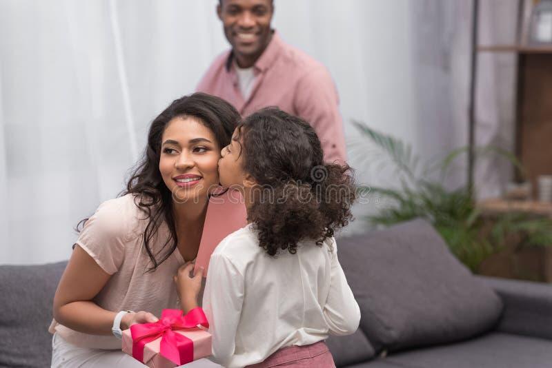 Dochter kussende moeder en het voorstellen van giften aan haar op moedersdag royalty-vrije stock foto's
