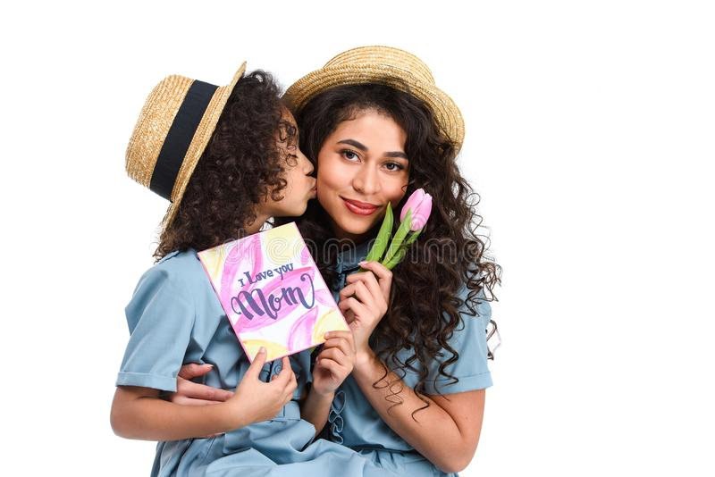 dochter met de groetkaart van de moedersdag en tulp die haar moeder kussen stock foto's
