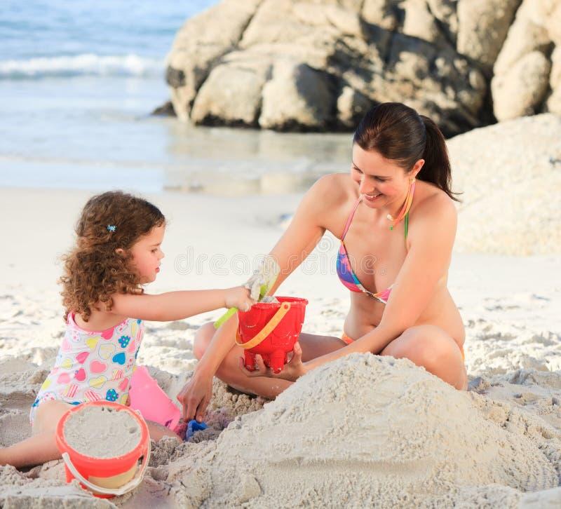 Dochter met haar moeder die een zandkasteel maakt royalty-vrije stock foto