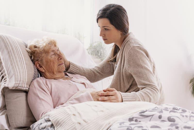 Dochter ondersteunend zieke moeder die in het ziekenhuisbed liggen stock afbeelding