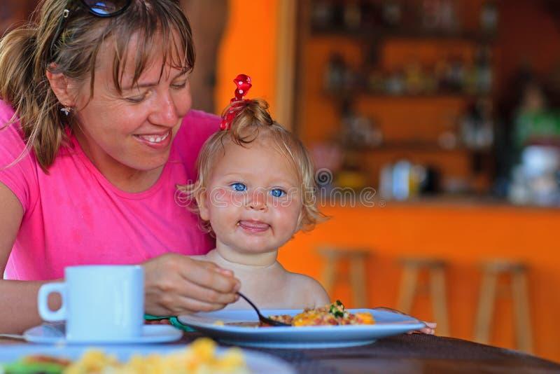 Dochter van de moeder de voedende zuigeling in koffie royalty-vrije stock afbeeldingen