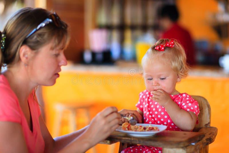 Dochter van de moeder de voedende zuigeling in koffie stock fotografie