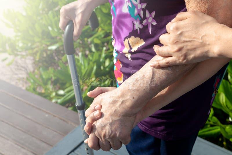 Dochter of zoons de hand van de greepmoeder om haar te helpen zorgvuldig te lopen stock afbeelding