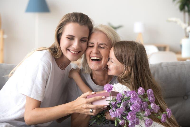 Dochterkleindochter en grootmoeder met giftdoos en bloemen binnen royalty-vrije stock afbeeldingen