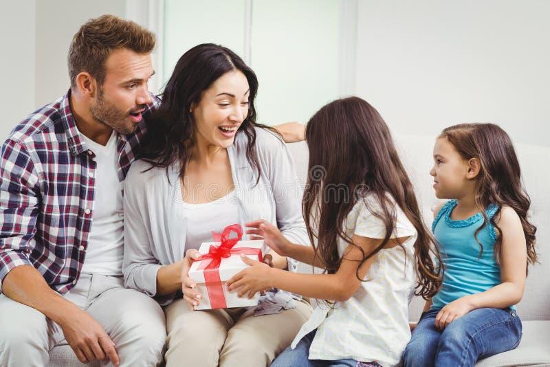 Dochters die gift geven aan verraste ouders stock foto