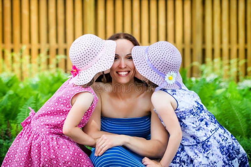 Dochters die hun Moeder op de Wang kussen stock fotografie