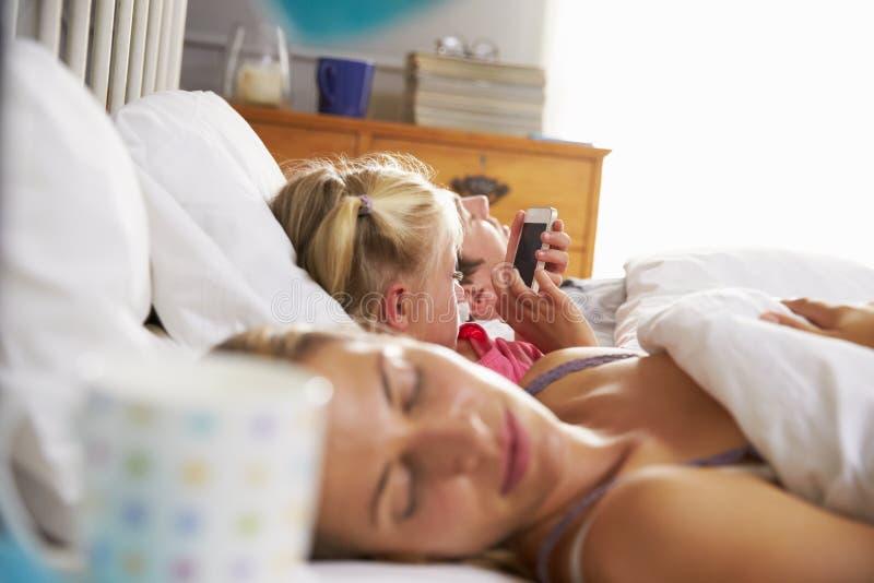 Dochterspelen met Mobiele Telefoon in Bed als Oudersslaap royalty-vrije stock afbeeldingen