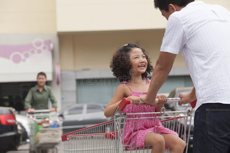 Dochterzitting in boodschappenwagentje en vader die, in openlucht voor supermarkt duwen stock fotografie