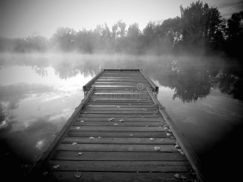 Dock auf nebeligem See des Sonnenaufgangs stockfotografie