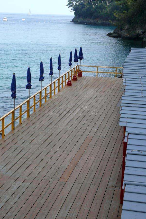 Dock, Blue Umbrellas Await the Italian Summer Sun. Blue umbrellas are still folded, and the dock is empty, awaiting the sun and bathers. Alight mist shrouds the vector illustration
