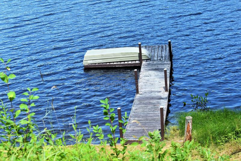 Dock and boat  on Leonard Pond, Colton,  St. Lawrence County, New York, United States. NY. US. USA. A landscape view of Leonard Pond, located near Tupper Lake royalty free stock photography