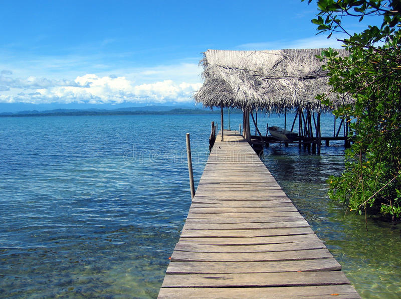 Dock with boathouse. And dug-out canoe and mangrove tree stock images