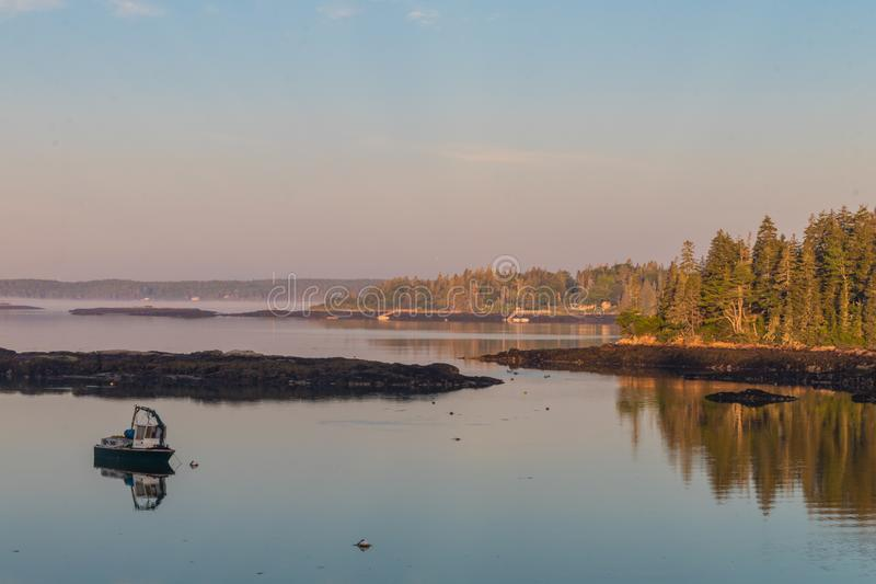 Dock and boats in bay in Boothbay, Maine, at sunrise in summer in soft beautiful light on reflective water. Coastal Maine stock photography