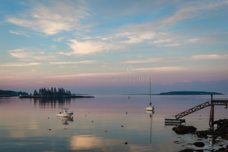 Dock and boats in bay in Boothbay, Maine, at sunrise in summer in soft beautiful light on reflective water. Coastal Maine royalty free stock photos
