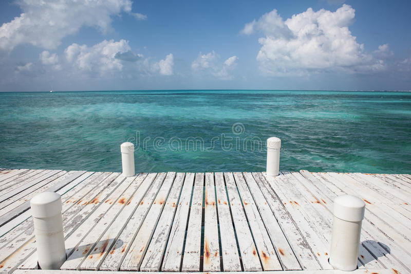 Dock and Caribbean Sea. A dock, on an island off the coast of Belize, is built on the edge of the Caribbean Sea stock image