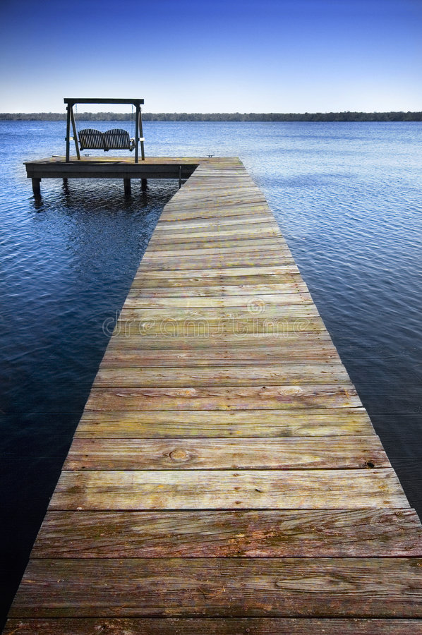 Dock and chairs. Portrait view of a wooden dock extending into a blue lake with small ripples. A swing sits at the end of the dock stock photography