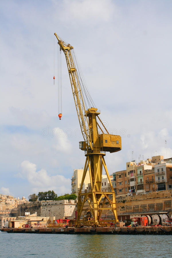 Dockside crane on wharf. A dockside crane standing on a wharf in Grand Harbour, Malta royalty free stock photos