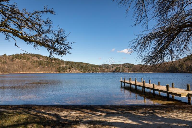 Dock durch den See in Norwegen, Vorfrühling bei Tjomsevannet in Sogne lizenzfreie stockfotos