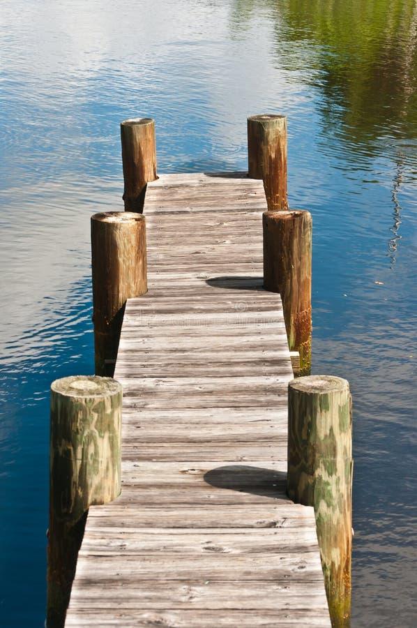Dock en bois de vintage avec six empilages en bois dans la crique tropicale photographie stock libre de droits