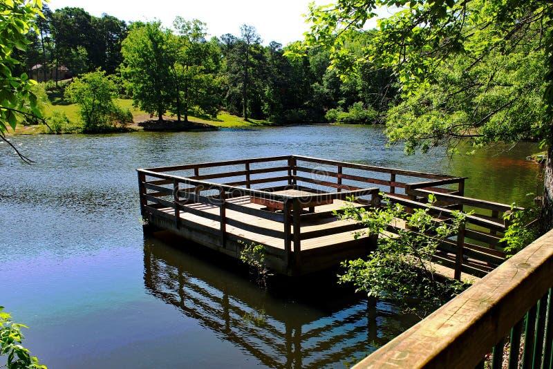 Dock flottant sur les arbres verts bleus de cieux bleus de printemps de lac photo libre de droits