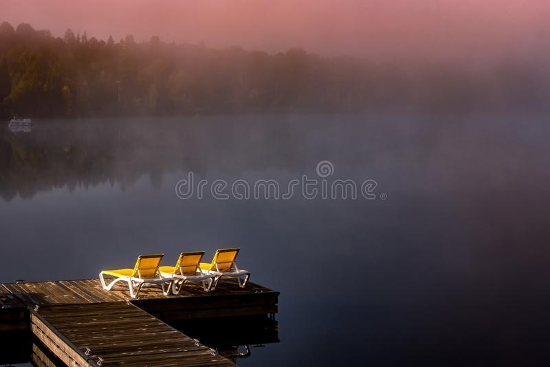 Dock on Lac Superieur, Mont-tremblant, Quebec, Canada. View of a boat dock the Lac Superieur, misty morning with fog, in Laurentides, Mont-tremblant, Quebec stock photography