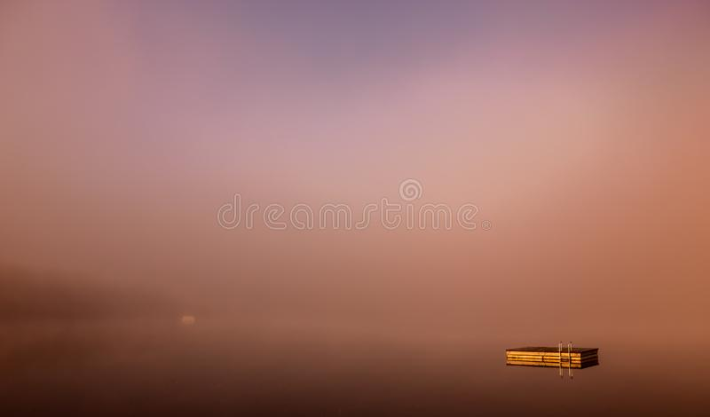 Dock on Lac Superieur, Mont-tremblant, Quebec, Canada. View of a boat dock the Lac Superieur, misty morning with fog, in Laurentides, Mont-tremblant, Quebec stock photos