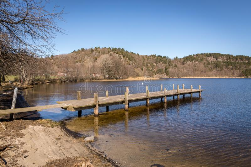 Dock by the lake in Norway, early spring at Tjomsevannet in Sogne. Dock by the lake in early spring. Blue water, blue sky. Tjomsevannet in Sogne, Norway stock photos