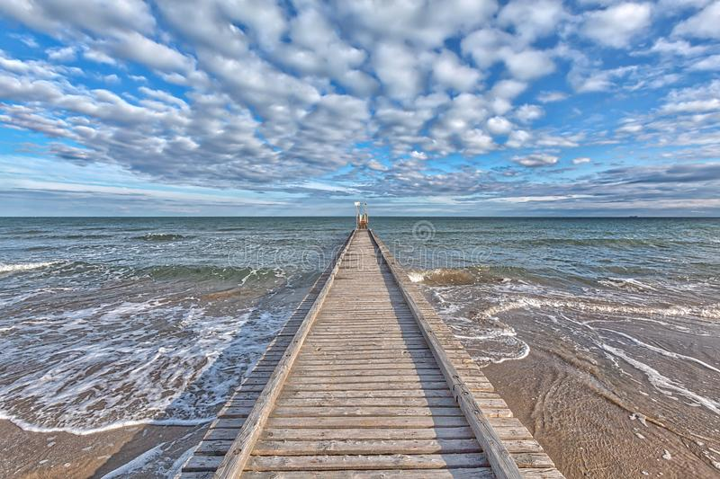 A dock leads to the mediterranean sea at the beach of Lido die Jesolo stock image