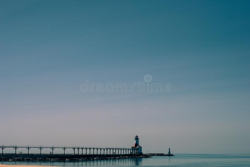 Dock Near White and Brown Concrete Lighthouse Surrounded by Calm Body of Water stock photo