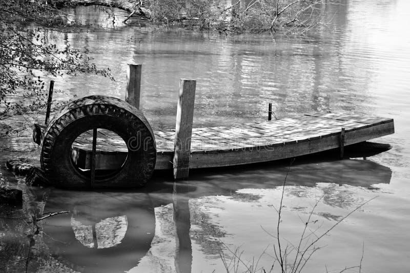 Dock noir et blanc, vieux, abandonné de bateau sur un petit lac images libres de droits