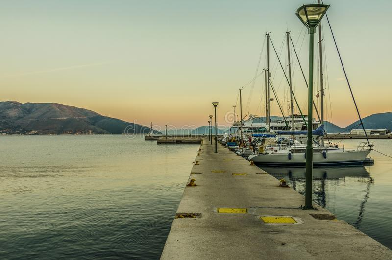 Dock of the port of Sami on the Ionian sea on the island of Kefalonia Greece. Dock and sailboats moored to it then the Ionian sea and finally the mountains at royalty free stock photo