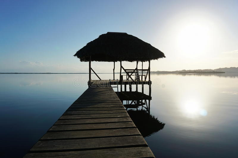 Dock with tropical hut over water on sunrise light royalty free stock photo