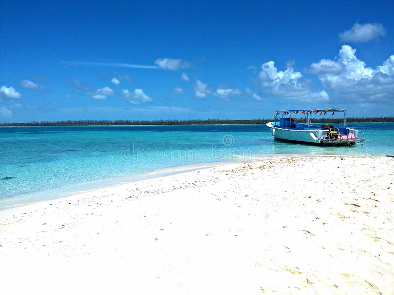 At The Dock. Tropical sandy beaches and aqua water with a fishing boat royalty free stock photography