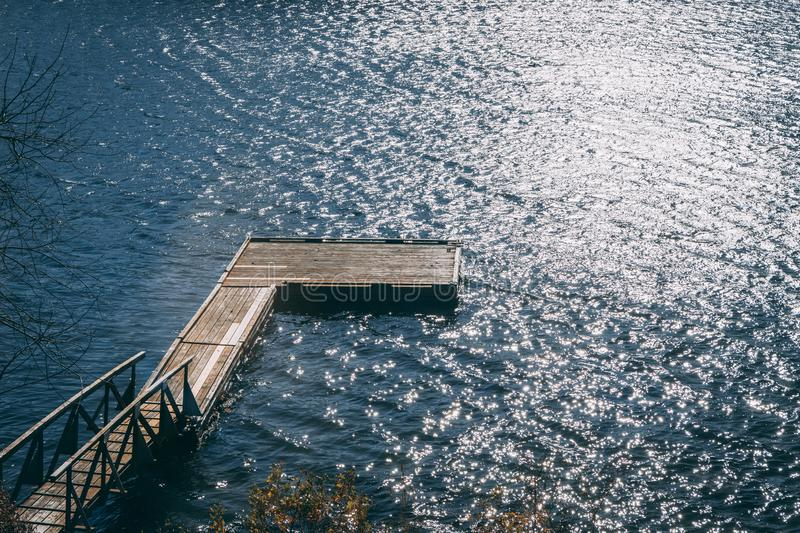 Dock on water with glaring sun. Boatless dock on wavy water with glaring sun in New England royalty free stock photos