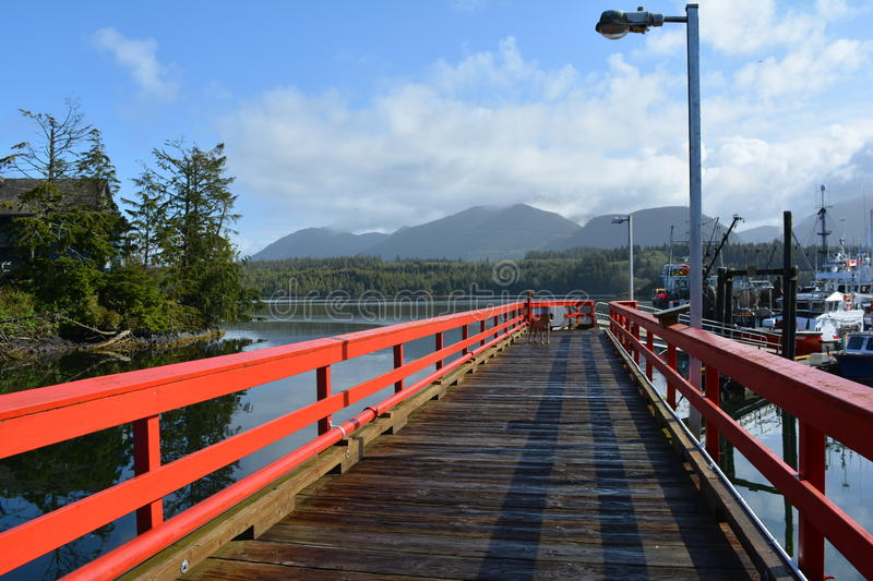 Dock in waterway, Ucluelit BC. Dock with red railings leading into waterway with boats somewhere in Ucluelit British Columbia. Japanese dock stock photo