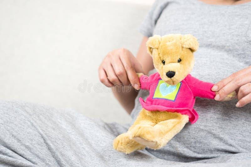 Docka för björn för nalle för lycklig gravid kvinnahand hållande på hennes buk w royaltyfri bild