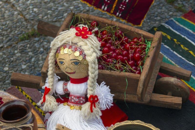 Docka i en typisk bulgarisk folkdräkt till en dekorativ vagn med körsbäret arkivbilder