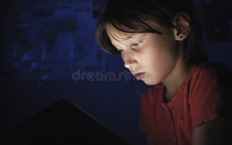 Docka skjuten caucasian flicka i säng som spelar minnestavlan i internet i mörker - blått ljus under blacket arkivfoton