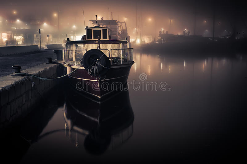 Docked boat in the fog stock images