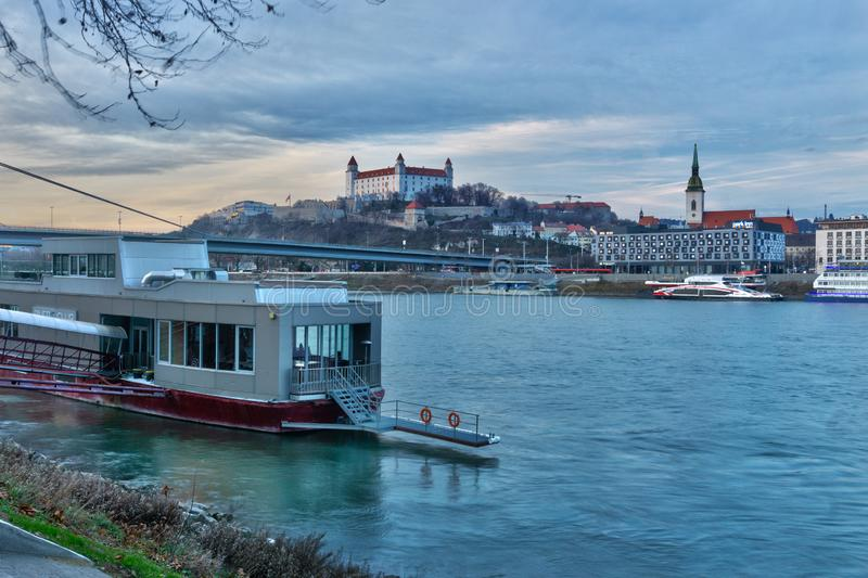 Docked ship at Danube river bank and Bratislava castle royalty free stock images