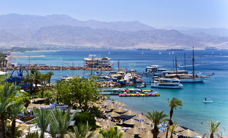 Docked yachts and boats in marina of Eilat, Israel. The shot was taken from the northern beach of Eilat city - a famous resort and recreation center of Israel royalty free stock image