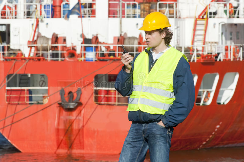 Docker. On the radio with instructions in front of a huge oil tanker in an industrial harbor stock image