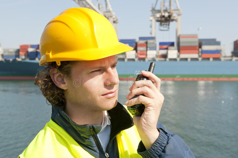 Docker on the radio. Harbor worker, listening to his radio for instructions royalty free stock image