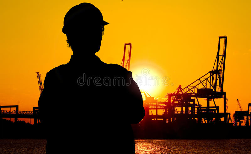 Docker at sunset. Silhouette of a docker, overlooking the cranes at the docks at sunset royalty free stock photo
